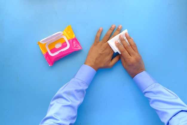 Mężczyzna dezynfekujący ręce wilgotną chusteczką na niebieskim tle