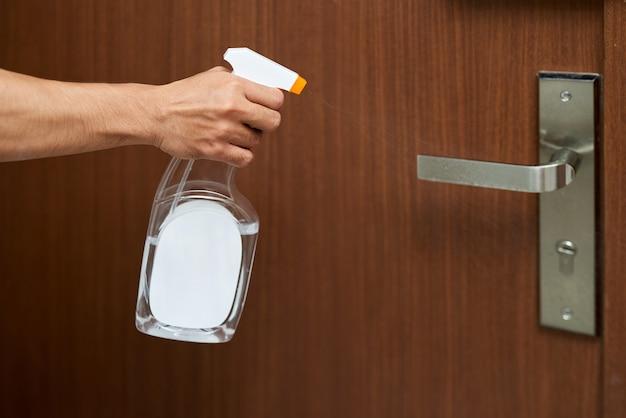 Mężczyzna dezynfekuje klamkę drzwi, rozpylając biały środek dezynfekujący z butelki