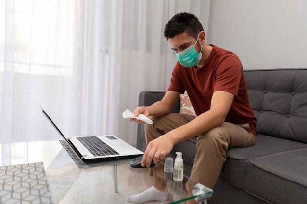 Mężczyzna dezynfekuje nieśmiałe powierzchnie, boi się zachorować.