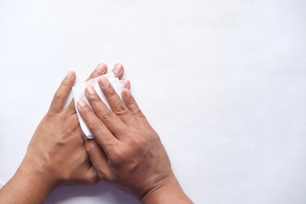 Mężczyzna dezynfekuje ręce wilgotną chusteczką na białym tle