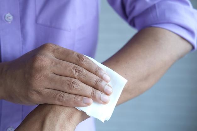 Mężczyzna dezynfekuje ręce wilgotną chusteczką