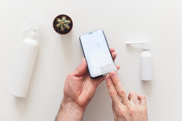 Mężczyzna dezynfekuje wycieranie smartfona chusteczką antybakteryjną, aby uchronić się przed koronawirusem covid-19. leżał płasko, na białym tle