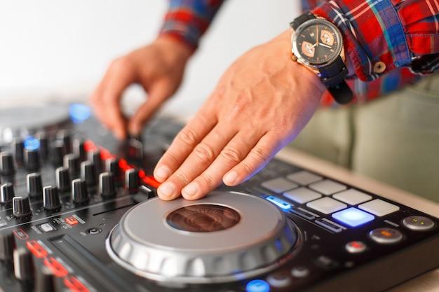 Mężczyzna dj gra na zbliżeniu konsoli mikserskiej