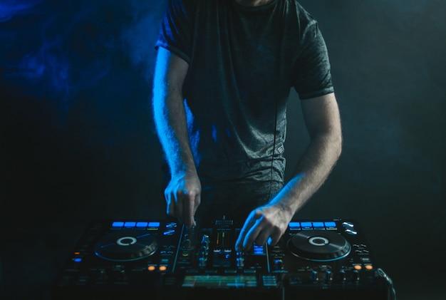 Mężczyzna dj pracuje pod światłami i dymem w ciemności