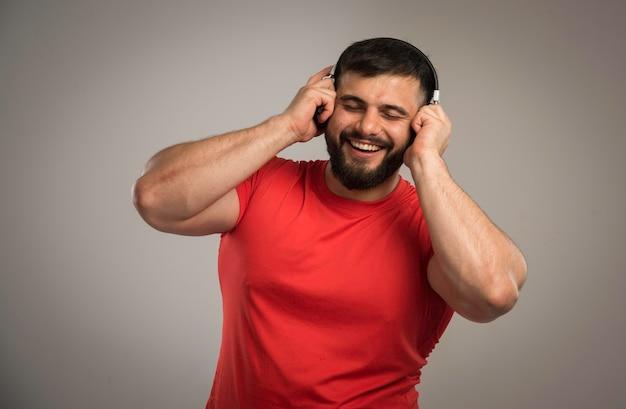 Mężczyzna dj w czerwonej koszuli na sobie słuchawki.