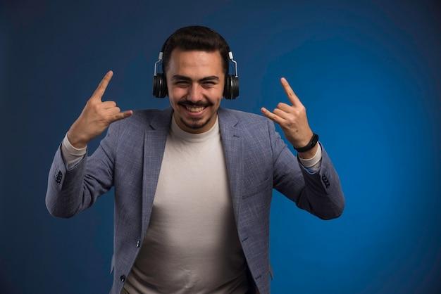 Mężczyzna dj w szarym garniturze, słuchając słuchawek i dobrze się bawiąc.