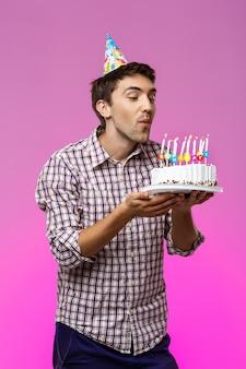 Mężczyzna dmucha świeczki na urodzinowym torcie nad purpury ścianą.