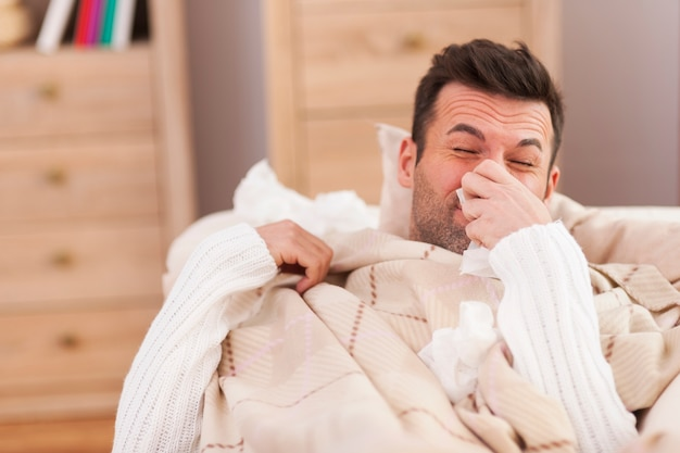 Mężczyzna dmuchający nos w łóżku