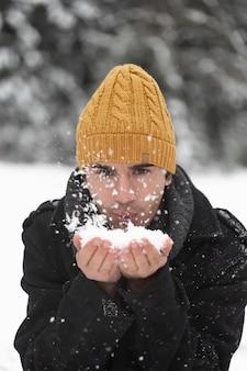 Mężczyzna dmuchanie w kupie śniegu widok z przodu