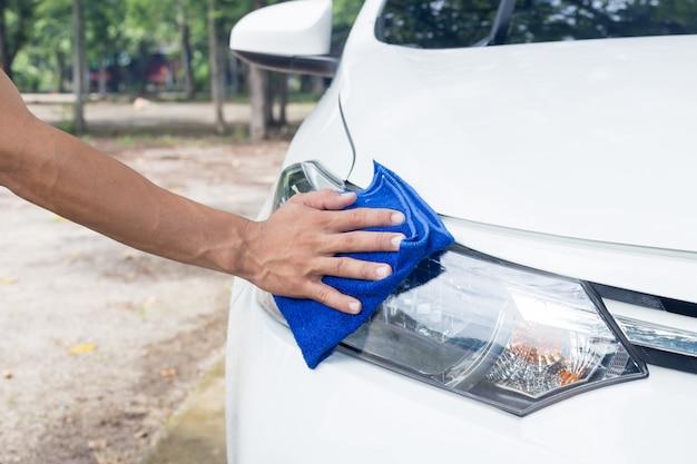 Mężczyzna do czyszczenia samochodu szmatką z mikrofibry - opisywanie szczegółów samochodu i waloryzacja