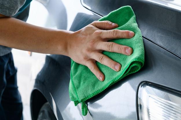 Mężczyzna do czyszczenia samochodu z zieloną szmatką z mikrofibry na masce samochodu