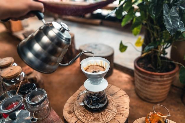 Mężczyzna dodając gorącą wodę do drippera kawy powyżej szklanego słoika.