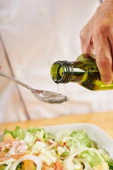 Mężczyzna dodaje olej do sałatki