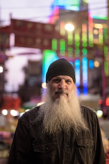 Mężczyzna dojrzały turysta z długą brodą w chinatown w nocy