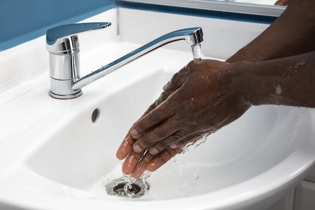 Mężczyzna dokładnie myje ręce mydłem i środkiem dezynfekującym, z bliska.