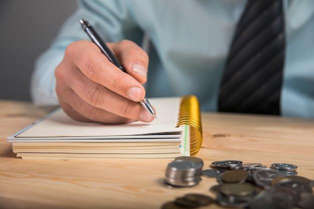 Mężczyzna dokonuje obliczeń i pisze w zeszycie