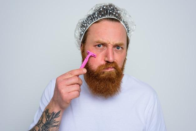 Mężczyzna dopasowuje brodę różową żyletką