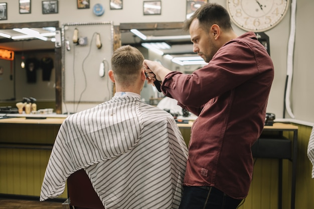 Mężczyzna dostaje ostrzyżenie przy zakładem fryzjerskim
