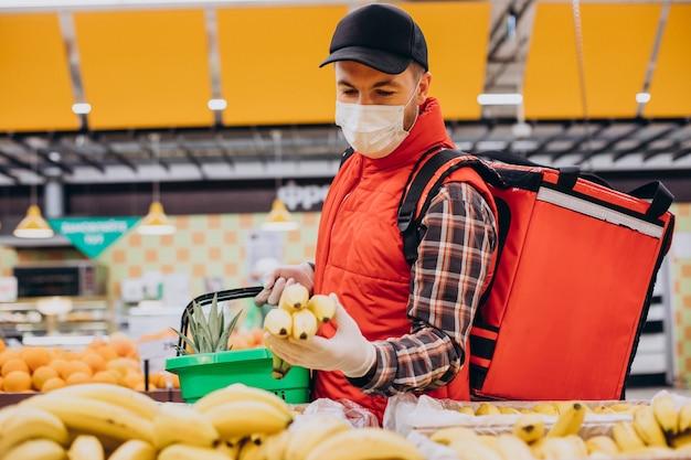 Mężczyzna dostarczający jedzenie, kupujący produkty w sklepie spożywczym