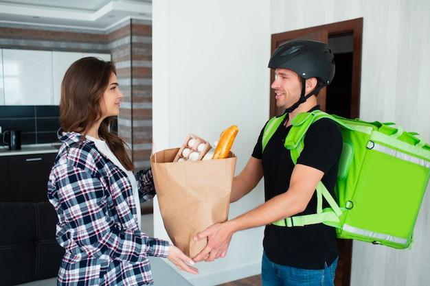 Mężczyzna dostarczający jedzenie przyniósł zamówienie do młodej dziewczyny. przyszedł w kasku na rowerze lub rowerze.