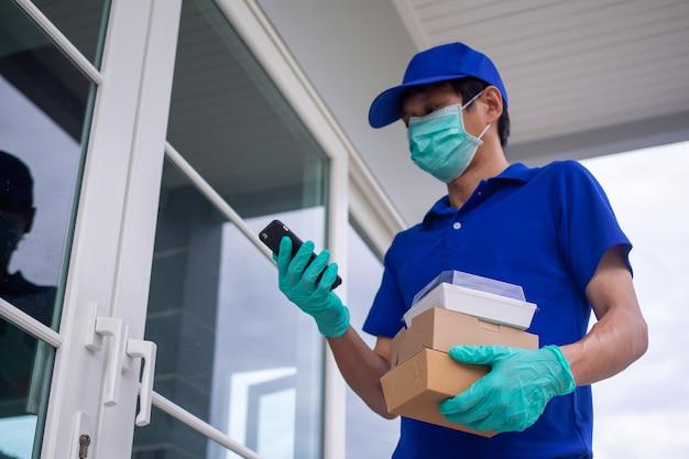 Mężczyzna dostarczający jedzenie w niebieskim mundurze, w masce i rękawiczkach, dostarcza jedzenie do klienta na wyciągnięcie ręki. personel wysyła jedzenie do klientów z zamówienia jedzenia online.