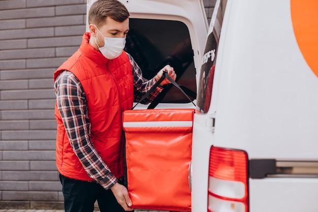 Mężczyzna dostarczający jedzenie wkłada pudełko z jedzeniem do samochodu