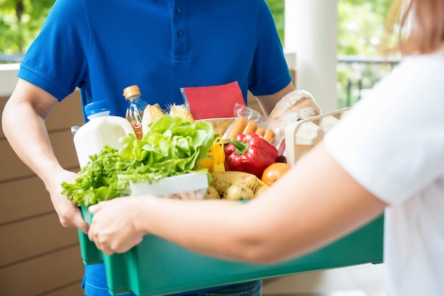 Mężczyzna dostawy agrocery dostarczania żywności do kobiety w domu