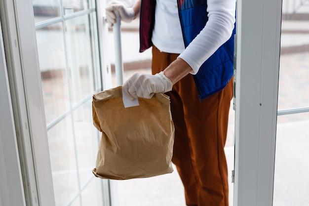 Mężczyzna dostawy artykułów spożywczych w rękawiczkach medycznych i maskę na twarz. zakupy online i dostawa artykułów spożywczych, wina i jedzenia. samodzielna kwarantanna podczas pandemii koronawirusa. kurier dostarczający jedzenie