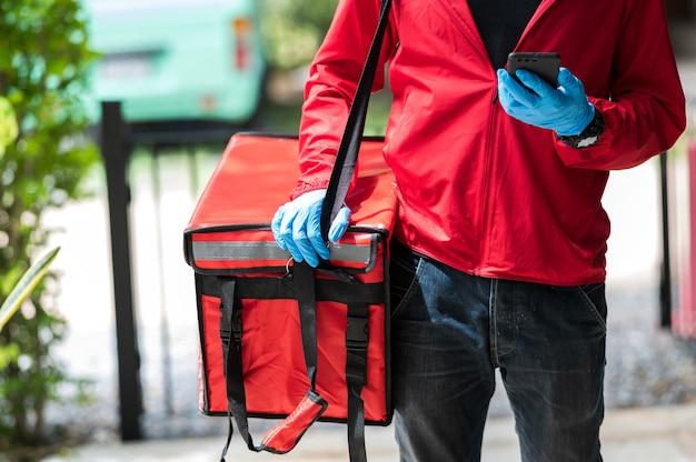 Mężczyzna dostawy czerwonej tkaniny szuka adresu klienta przez telefon komórkowy