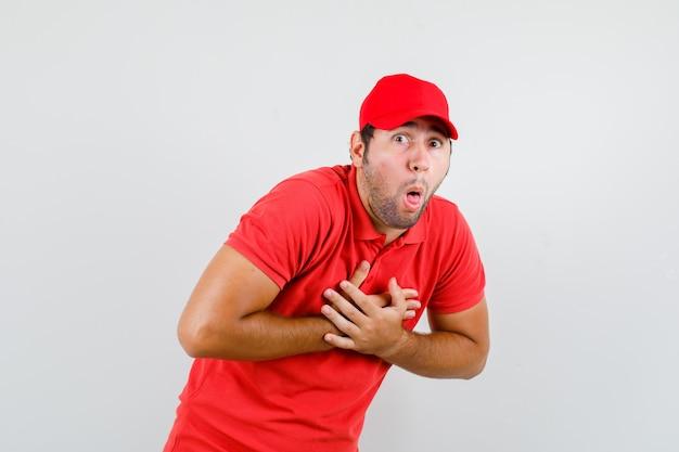 Mężczyzna dostawy czuje mdłości z rękami na klatce piersiowej w czerwonej koszulce