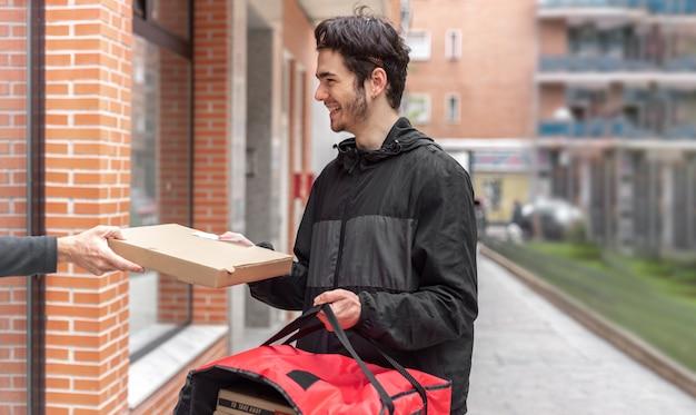 Mężczyzna dostawy dostarczający żywność do domu klienta, trzymając czerwoną torbę