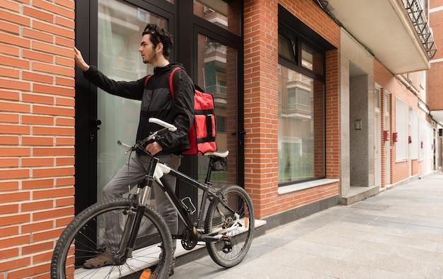 Mężczyzna dostawy dzwoni do odźwiernego, trzymając czerwoną torbę na dostawę do domu żywności z rowerem