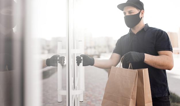 Mężczyzna dostawy mężczyzna w czarnym mundurze z torby