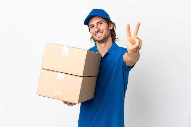 Mężczyzna dostawy na białym tle na białej ścianie, uśmiechając się i pokazując znak zwycięstwa