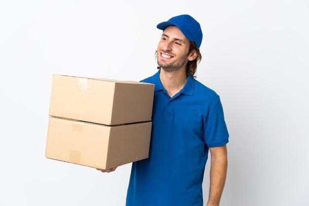 Mężczyzna dostawy na białym tle na białym tle, patrząc z boku i uśmiechnięty