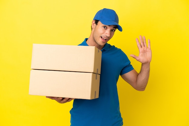 Mężczyzna dostawy nad odosobnioną żółtą ścianą pozdrawiając ręką ze szczęśliwym wyrazem twarzy