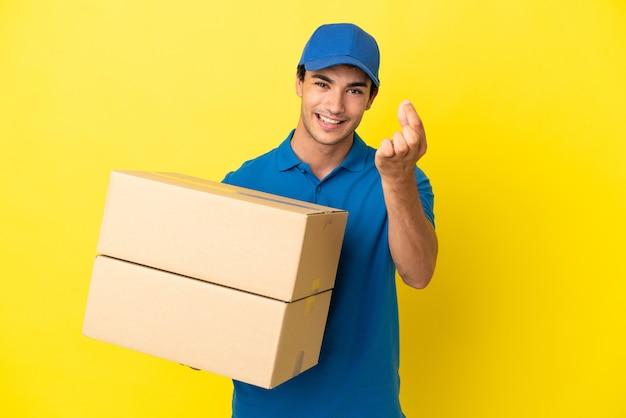 Mężczyzna dostawy nad odosobnioną żółtą ścianą robienia pieniędzy gest