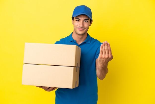 Mężczyzna dostawy nad odosobnioną żółtą ścianą, zapraszając do przyjścia z ręką. cieszę się, że przyszedłeś