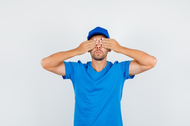 Mężczyzna dostawy obejmujące oczy rękami w niebieskiej koszulce