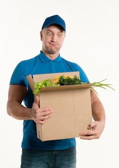 Mężczyzna dostawy patrząc głupio na pudełko spożywcze