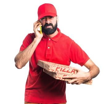 Mężczyzna dostawy pizza rozmawia z telefonu komórkowego