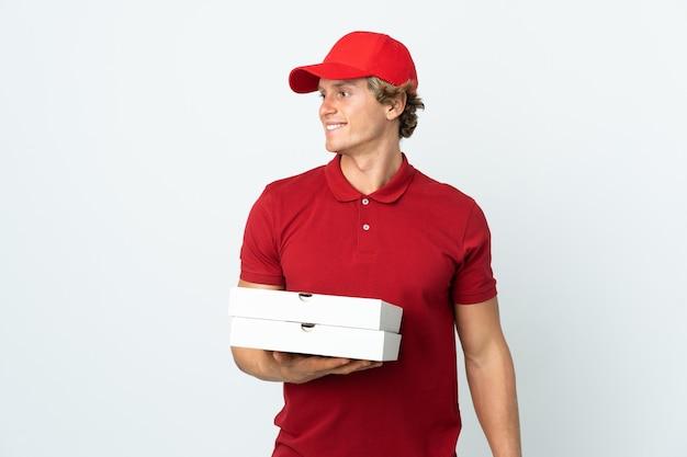 Mężczyzna dostawy pizzy na białym tle patrząc z boku i uśmiechnięty