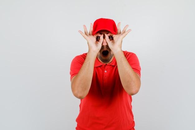 Mężczyzna dostawy pokazując gest okulary z otwartymi ustami w czerwonej koszulce