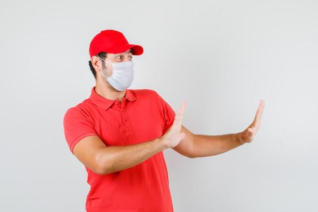Mężczyzna dostawy pokazując gest stopu w czerwonej koszulce