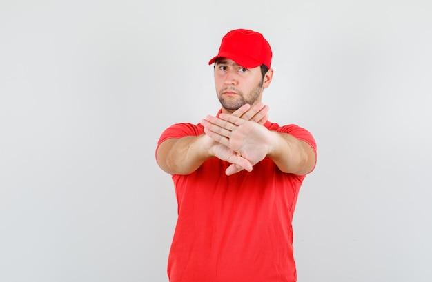 Mężczyzna dostawy pokazujący gest odmowy w czerwonej koszulce