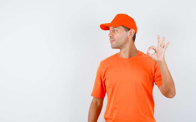Mężczyzna dostawy pokazujący znak ok, patrząc na bok w pomarańczowej koszulce i czapce i wyglądający wesoło