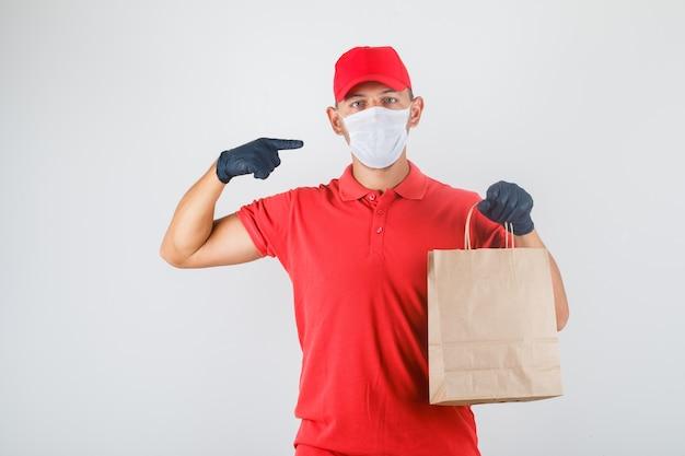 Mężczyzna dostawy, trzymając papierową torbę i wskazując się w czerwonym mundurze, masce medycznej, rękawiczkach