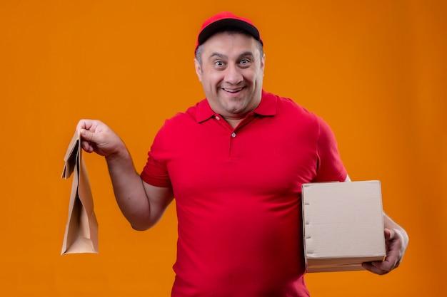 Mężczyzna dostawy ubrany w czerwony mundur i czapkę, trzymając papierowy pakiet i karton, wyglądający na zaskoczonego i szczęśliwego na pomarańczowej ścianie
