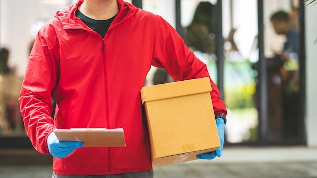 Mężczyzna dostawy ubrany w niebieskie rękawiczki i czerwoną kurtkę, trzymając karton i schowek
