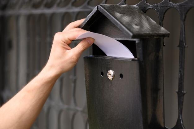 Mężczyzna dostawy z bliska upuszczanie koperty w skrzynce pocztowej